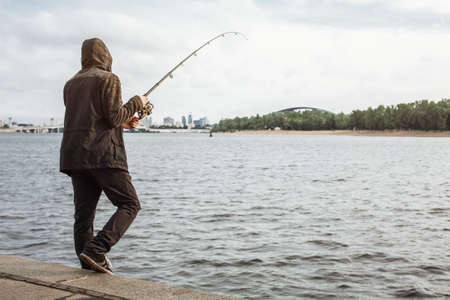 Young man fishing with a spinning on the river Stock Photo