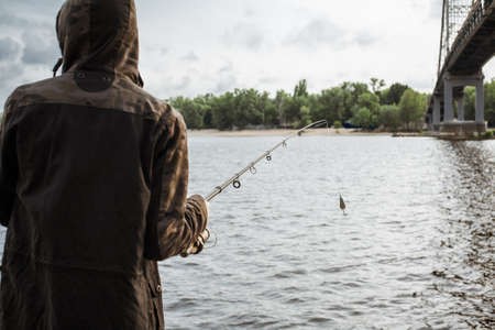 Young man fishing on the river. Fisherman holding spinning rod with spoon bait