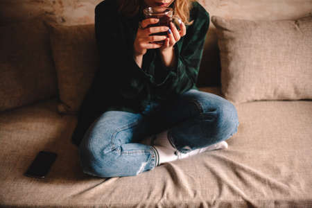 Young woman drinking tea while sitting on sofa at home Stock Photo