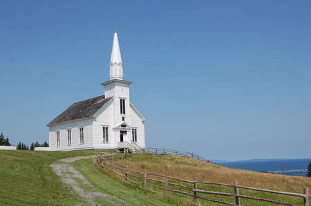 nova scotia: old white church in nova scotia, canada, overlooking the sea on summers day