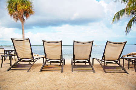 beach front: four loungers line the beach front  Stock Photo