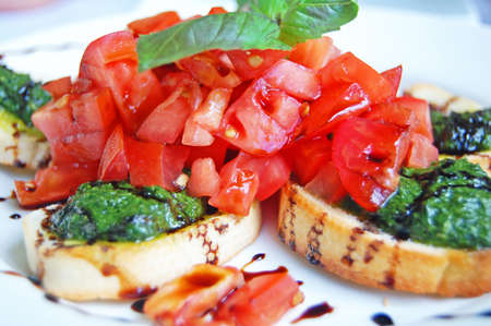 bruschetta topped with chopped tomato and pesto with balsamic Stock Photo