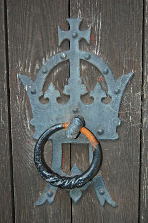 close up of a door knocker on old wooden door photo