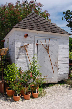 white rustic garden potting shed in summer