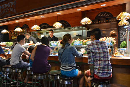 boqueria: Barcelona - August 21: customers seated at a tapas bar at La Boqueria market in Barcelona, Spain on Augut 21, 2014. The market is one of the oldest in Europe and a popular tourist attraction.