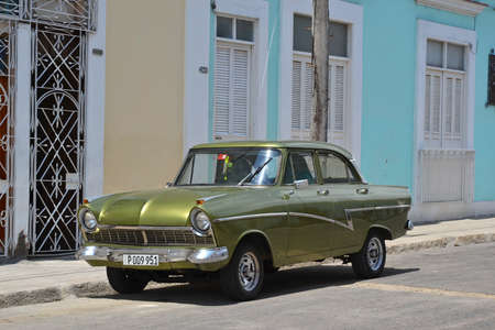 maintained: Cienfuegos - July 24: a green classic Ford car parked in a street in Cienfuegos, Cuba on July 24, 2014. Many classic cars continue to be maintained and privately owned by Cubans.