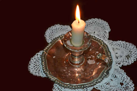 burning candle in antique victorian silver holder against a black background