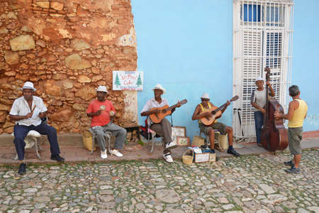 the throughout: Trinidad - July 27: musicians play in the street in Trinidad, Cuba on July 27, 2014. Cuban music is popular throughout the world and is influenced by West African and Spanish music. Editorial