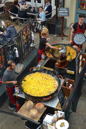 covent: London - September 13: chefs cooking giant paellas at a restaurant in Covent Garden, London, UK on September 13, 2014. The old vegetable market is now a major tourist attraction with shops, pubs and restaurants.