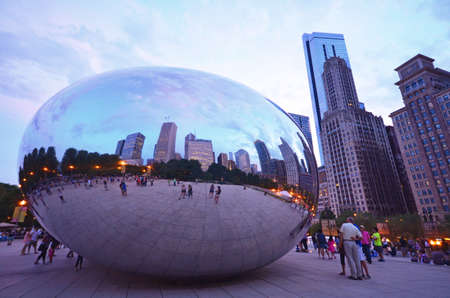 Chicago - August 14: tourists at the Bean at twilight in Chicago, USA on August 14, 2015. The sculpture, known as Cloud Gate, is located in Millenium Park and is a popular tourist attraction.