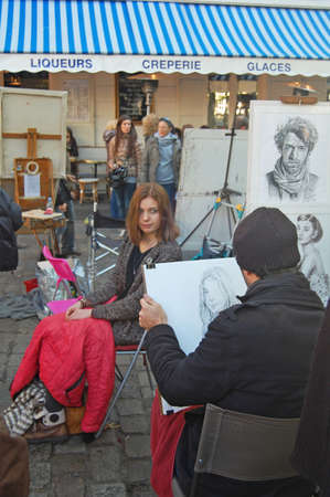 Montmartre, France - October 31, 2012: Place du Tertre in Montmartre, Paris with street artist doing portrait of young woman. The area is a popular tourist attraction in Paris.