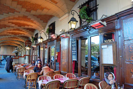 Paris - October 31, 2012: people sat outside a restaurant in Place des Vosges, Paris, France. The city is known for its many bars and restaurants with outdoor seating. Editorial