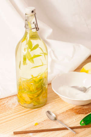 Bottle of brandy with verbena leaves , sugar, lemon peel. Preparation of liquor in the house on a white background.
