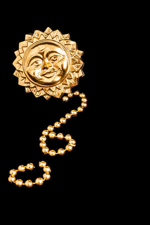 string of pearls: Background or texture with a gold sun in relief and a string of fake gold pearls