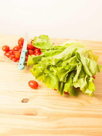 tabel: Head of lettuce and tomatoes on a light wooden table Stock Photo