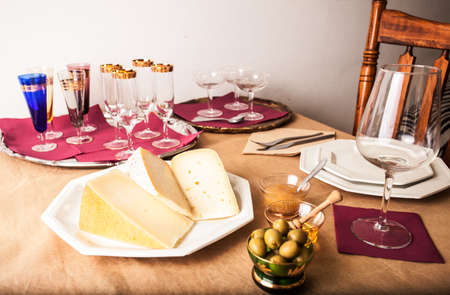 gold table cloth: Table elegantly laid with Italian cheese appetizer, pitted olives, honey and pear marmalade. Stock Photo