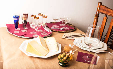 gold table cloth: Table elegantly laid with the Italian cheese appetizer, pitted olives, honey and pear marmalade.