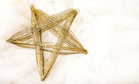 background texture metaphor: Golden star ornament on a white tulle fabric, appropriate for a card or texture Stock Photo