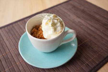 Coffee granite with white chocolate foam and wild fennel, in a blue cup with disch, ambient light. Stock Photo