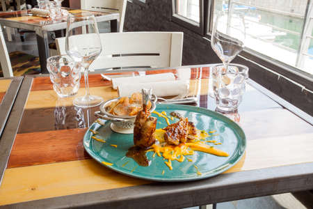 Italian chefs recipe in a restaurant, rooster with potato puree and potato chips with oregano and capers. Light ambient.