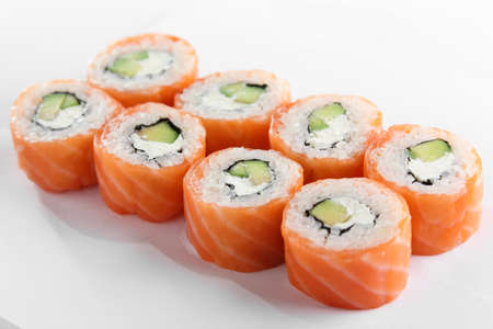 fresh and tasty sushi on bright background photo