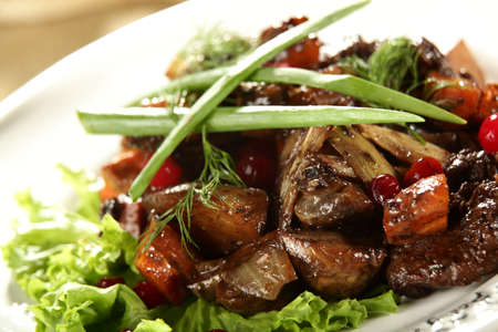 fine dining: salad with meat and berries on the white dish