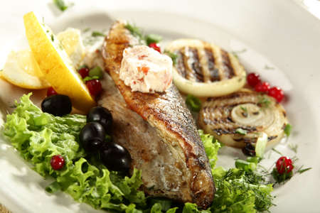 hot fish in white dish with olives and lemon photo