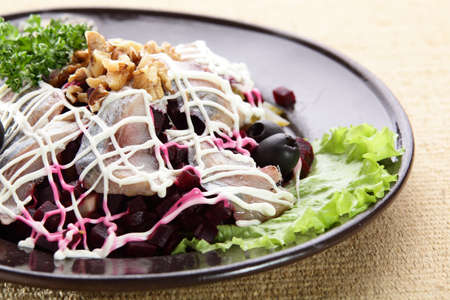 salad with fish and nuts in black dish photo