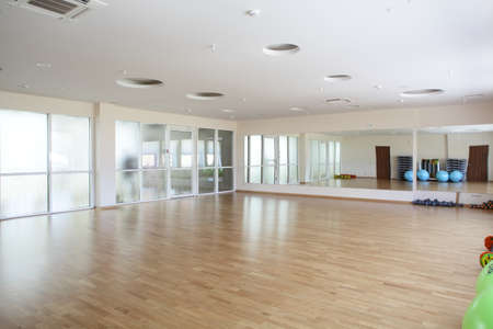 gym room: empty and full of light european gymnasium with big mirror