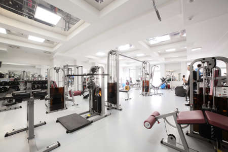 exercise room: interior of new modern gym with equipment