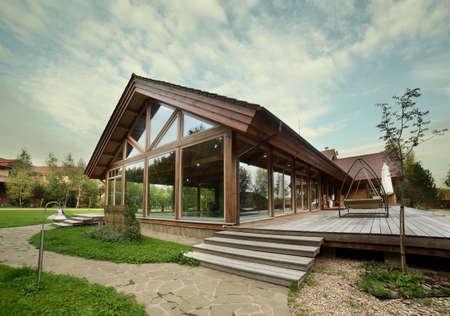 luxe houten huis met bomen en zwembad