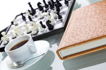orange leather book on bright background and chess photo