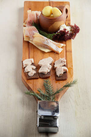salty fish assorti with potato and herbs on wooden plate photo