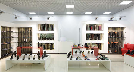 window display: bright and fashionable interior of shoe store in modern mall