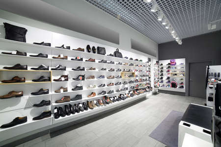 clothing store: bright and fashionable interior of shoe store in modern mall
