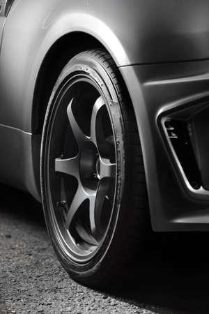 close up of grey car wheel on asphalt