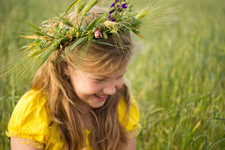 Beautiful little girl on the meadow. A wreath of wheat ears  and wild flowers is on her blonde hair photo