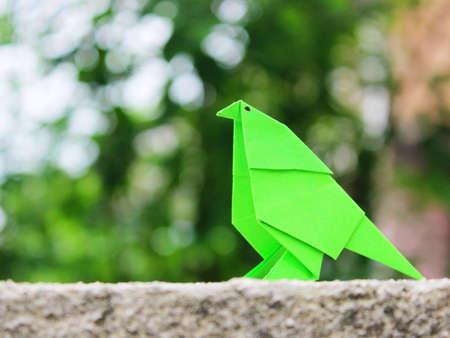 green bird origami with circle bokeh