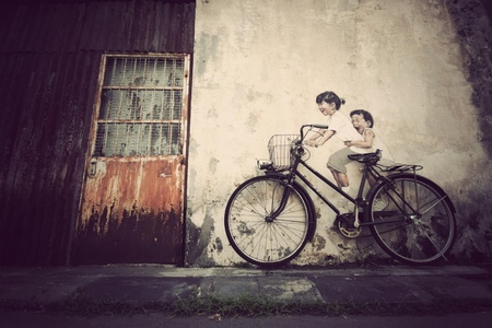 the mural: mural painting kids ride a bicycle Stock Photo