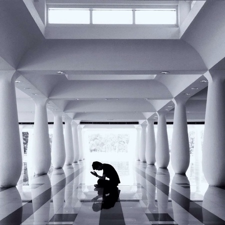 silhouette of man praying in mosque Stock Photo