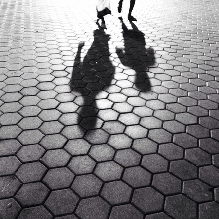 shadow of two people walking on honey comb pattern