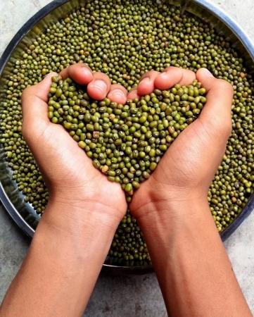 hand full of green beans shaping love