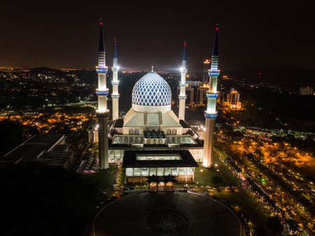 Beautiful aerial night shot of Sultan Salahuddin Abdul Aziz Shah Mosque, an iconic mosque that is also known as Shah Alam Mosque with city scape in the background Stok Fotoğraf