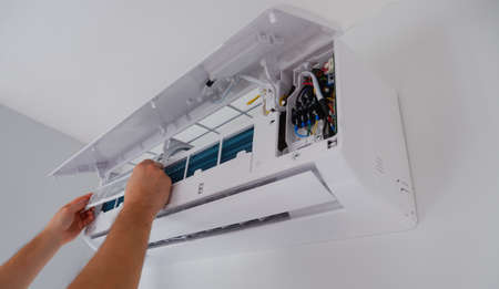 Air conditioner repair and maintenance. The technician removes the filter of the indoor unit for cleaning. Archivio Fotografico