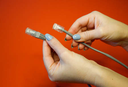 RJ45 network connector on a red background in well-groomed female hands