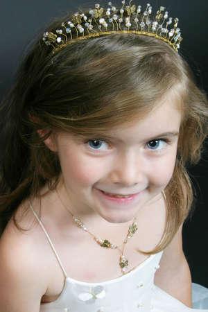 flowergirl: Cute girl wearing a tiara and flower-girl dress � studio portrait