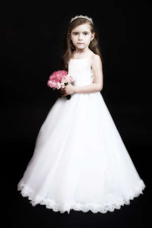 Cute girl with roses and in flower-girl dress – studio portrait on black background, old finish photo