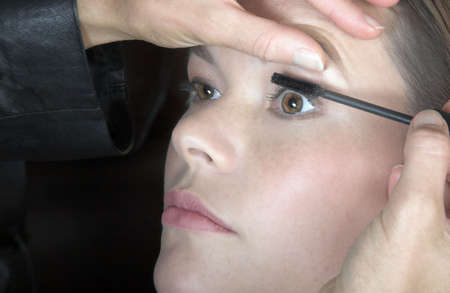 womanhood: Make-up artist applying mascara to young woman's lashes