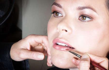 womanhood: Make-up artist applying lipstick to young woman�s lips