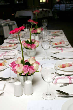 wedding table setting with pink and white roses and pink daisies photo